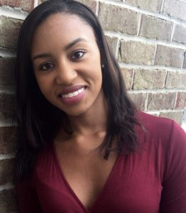 Therapist for College Students in Maryland Maya Jefferson leaning against a brick wall